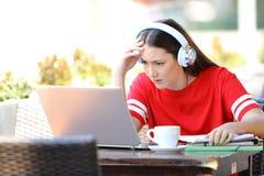 与一台膝上型计算机的担心的学生电子教学在咖啡馆 免版税图库摄影