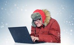 与一台膝上型计算机的程序员在冬天飞雪 库存照片