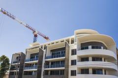 与一台起重机的现代大厦精整在蓝天下 免版税库存图片