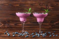 与一名新鲜的圆滑的人的两块玻璃 在木背景的鲜美圆滑的人 自然饮料用蓝莓、薄菏和莓 库存图片