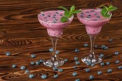与一名新鲜的圆滑的人的两块玻璃 在木背景的鲜美圆滑的人 自然饮料用蓝莓、薄菏和莓 图库摄影