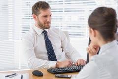 与一名co工作者的商人会谈他的书桌的 免版税库存图片
