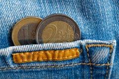 与一和两在破旧的蓝色牛仔布牛仔裤的口袋的欧元的衡量单位的两枚欧洲硬币 免版税库存照片
