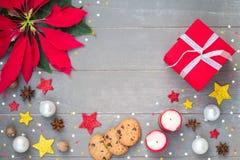 与一品红圣诞节、蜡烛、礼物和星的圣诞节装饰在灰色木背景 免版税库存照片