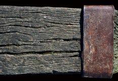 与一块生锈的金属板材的被风化的木粱 免版税库存照片