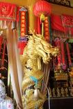 与一块红色布料的美丽的金黄佛教雕象龙 免版税图库摄影