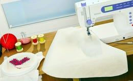 与一块缝纫机、刺绣、细节和布料的静物画 图库摄影