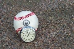 与一块老体育秒表的新的棒球 免版税库存照片