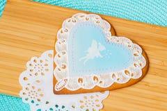 与一块逗人喜爱的小女孩矮子和网眼图案小垫布,背景木板条的图象的美丽的淡色蓝色姜饼 库存图片