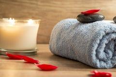 与一块滚动的蓝色毛巾的豪华温泉设置,浪漫蜡烛 免版税库存照片