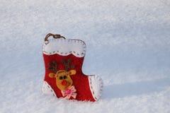 与一头滑稽的鹿的圣诞节袜子在雪 库存图片