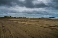 与一家旅馆的一个宽沙子海滩在天际结束时在长滩华盛顿在风雨如磐的秋天晚上 库存照片