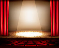与一幅红色帷幕、位子和聚光灯的一个剧院阶段 库存照片