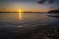 与一座冰山的日落视线内沿一个海岸地区的 免版税图库摄影