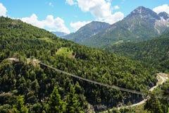 与一座吊桥和山的史诗山风景在背景中 免版税库存图片