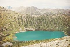 与一座小山和湖的美好的山风景 免版税库存照片