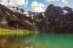 与一座小山和湖的美好的山风景 免版税库存图片