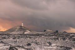 与一座灯塔的一个多雪的领域在小山在冰岛 库存图片