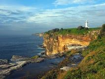 与一座白色灯塔的海洋峭壁 免版税库存图片