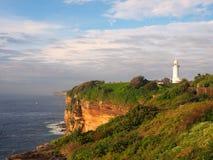 与一座白色灯塔的海洋峭壁 免版税库存照片