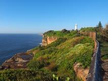 与一座白色灯塔的海洋峭壁 图库摄影
