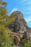 与一座石桥梁的山景在马拉加省 免版税库存图片