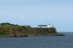 与一座老灯塔的陡峭的海海角 免版税图库摄影