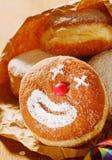 与一张愉快的小丑面孔的奶油色多福饼 库存图片