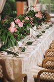 与一张白色桌布的一张美丽的桌,晚餐会的板材,装饰用棕榈树的叶子,白色 库存照片