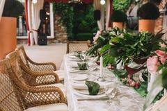 与一张白色桌布的一张美丽的桌,晚餐会的板材,装饰用棕榈树的叶子,白色 免版税图库摄影