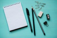与一张空白页的笔记薄,笔,两支铅笔,橡皮擦,金属在绿松石背景截去 免版税库存照片