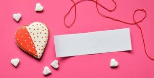 与一张空的纸的自创姜饼心脏您的在桃红色背景的文本的 华伦泰曲奇饼心脏 可食的华伦泰Da 图库摄影