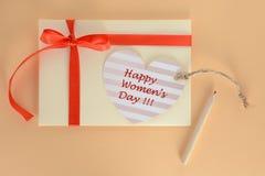 与一张红色丝带和心脏愉快的妇女天卡片的淡黄色信封在杏子背景 免版税库存照片