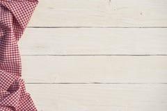 与一张红色方格的桌布的白色木背景 免版税库存图片