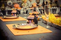与一张黑桌布的招待会桌和装饰为万圣夜集会,一个小纸板房子、玻璃和板材在纸盒 免版税库存图片