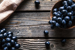 与一张洗碗布的蓝色葡萄在木背景 食物,果子 图库摄影