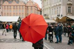 与一把传统红色伞的一个指南在老镇中心在布拉格邀请游人参观视域 旅游业 库存照片