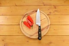 与一把刀子的三个红辣椒在一块砧板 免版税库存图片