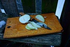 与一把刀子的切的葱在篱芭附近的一个木板在雪的街道 库存图片