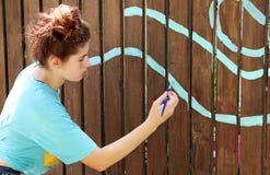 与一把刷子的一个十几岁的女孩油漆在棕色篱芭 库存照片