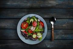 与一把匙子的新鲜蔬菜沙拉在色的木背景 顶视图 图库摄影