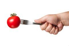 与一把叉子的一个完善的红色蕃茄在它 免版税库存照片