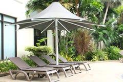 与一把大伞的松弛藤条椅子在游泳池旁边 免版税库存照片