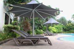 与一把大伞的松弛藤条椅子在游泳池旁边 库存图片