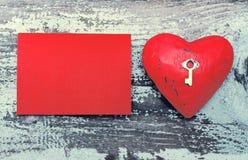 与一把小金属钥匙的红色心脏和与空间的一个空白的红牌文本的 库存照片