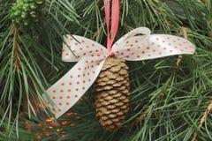 与一把弓的冷杉球果在一条红色丝带以杉木针为背景和一个家庭壁炉的火的红色豌豆 免版税库存照片