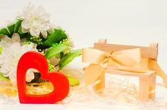 与一把弓的木心脏在白色背景的一条长凳 日s华伦泰 爱的概念 言情 免版税图库摄影