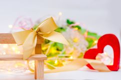 与一把弓的木心脏在白色背景的一条长凳 红色上升了 爱的概念 言情 高雅 免版税库存图片