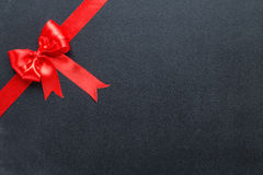 与一把弓的红色丝带在黑人委员会 免版税库存图片