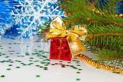 与一把弓的红色圣诞节礼物在圣诞树下 免版税库存照片
